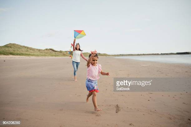 mother and daughter playing on the beach with a kite - northumberland stock pictures, royalty-free photos & images