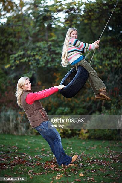 mother and daughter (7-9) playing on tyre swing, portrait - brown jeans stock photos and pictures