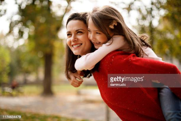mother and daughter playing outdoor - damircudic stock photos and pictures