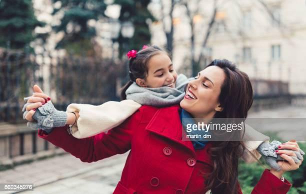 mutter und tochter spielen draußen - kindertag stock-fotos und bilder