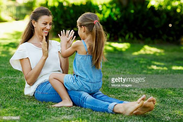 mother and daughter playing pattycake in park - girls barefoot in jeans stock photos and pictures
