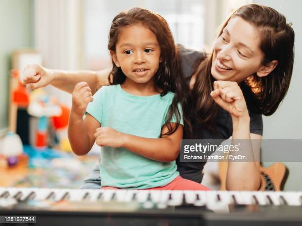 mother and daughter playing piano at home - hamiltonmusical stockfoto's en -beelden