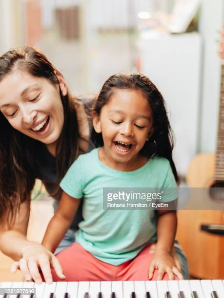 mother and daughter playing piano at home - hamiltonmusical stock pictures, royalty-free photos & images