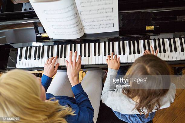 Mother and daughter playing piano at home