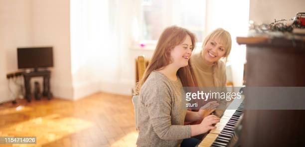 mother and daughter playing piano - down syndrome stock pictures, royalty-free photos & images