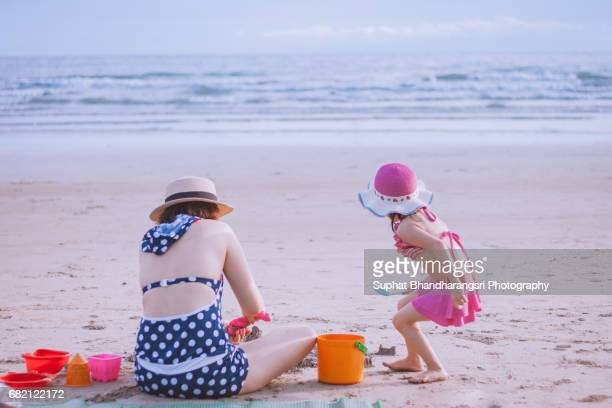 Mother and daughter playing sand toys