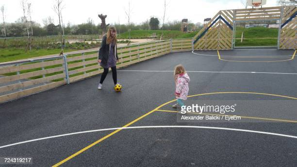 mother and daughter playing soccer on court - milton keynes stock pictures, royalty-free photos & images
