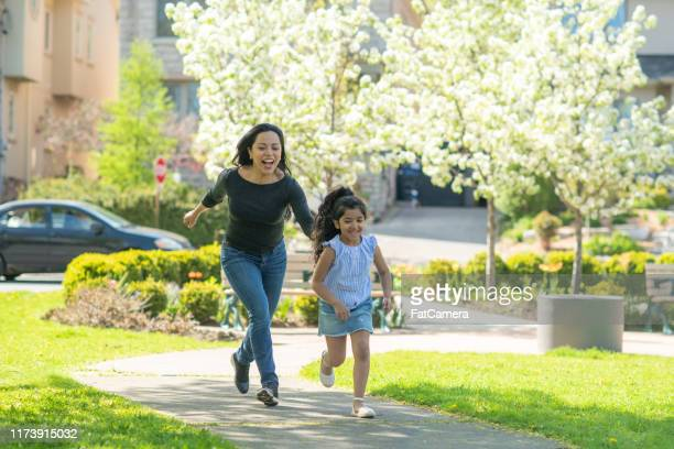 mother and daughter playing tag - fatcamera stock pictures, royalty-free photos & images
