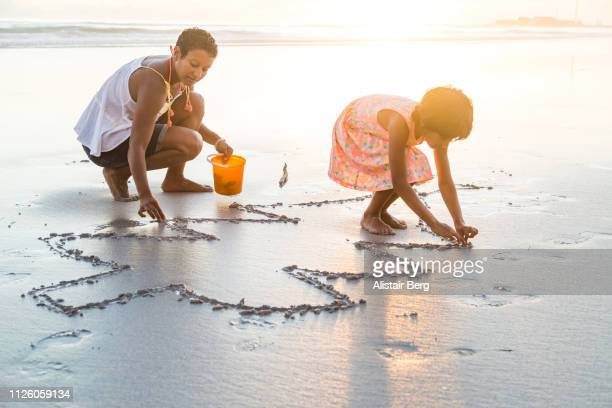 Mother and daughter playing together on the beach
