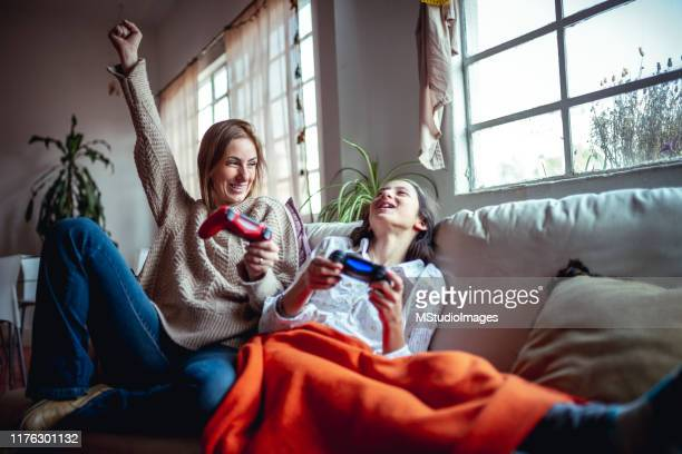 mother and daughter playing video games - giochi per bambini foto e immagini stock