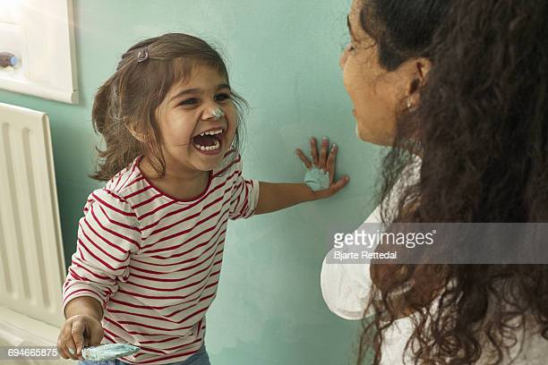 Mother and Daughter playing while decorating room