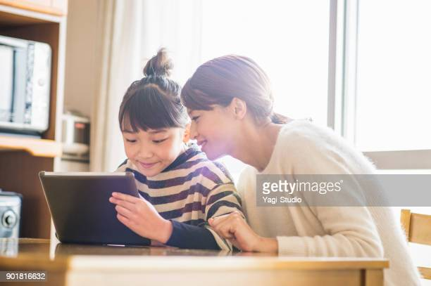 mother and daughter playing with a digital tablet in room - one parent stock pictures, royalty-free photos & images