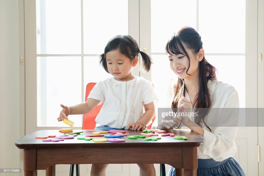 Mother and daughter playing with alphabet toy : ストックフォト