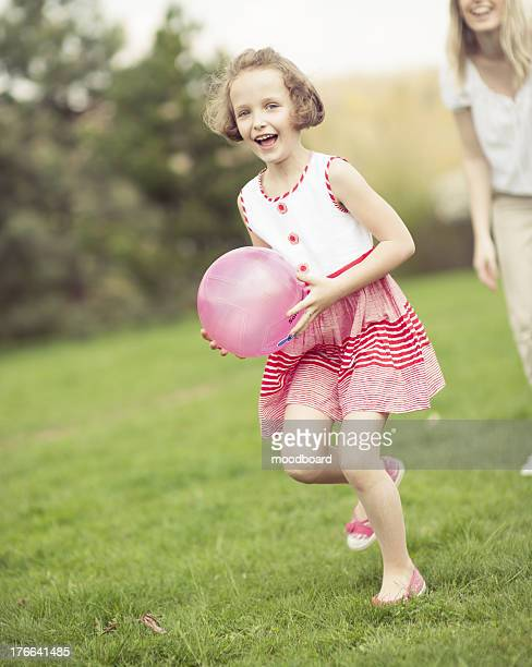 Mother and daughter playing with ball in the park