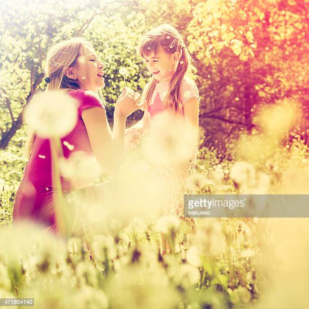 Mother and daughter playing with dandelions in nature