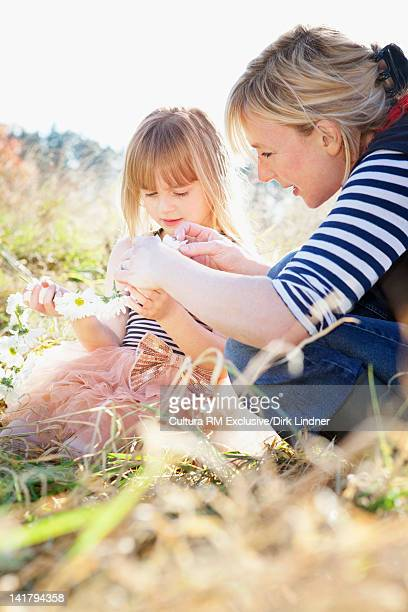 Mother and daughter playing with flowers