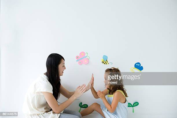 Mother and daughter playing with hands, side view