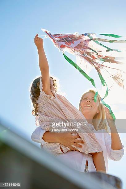 mother and daughter playing with kite, utvalnas, gavle, sweden - kite toy stock photos and pictures