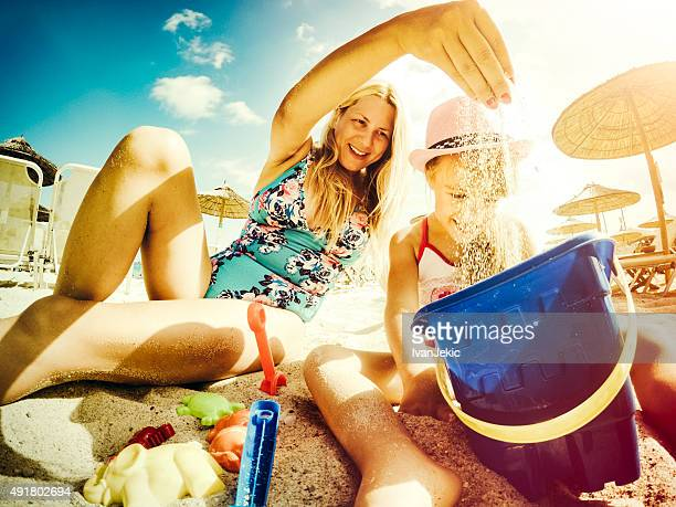 Mother and daughter playing with sand on beach with toys