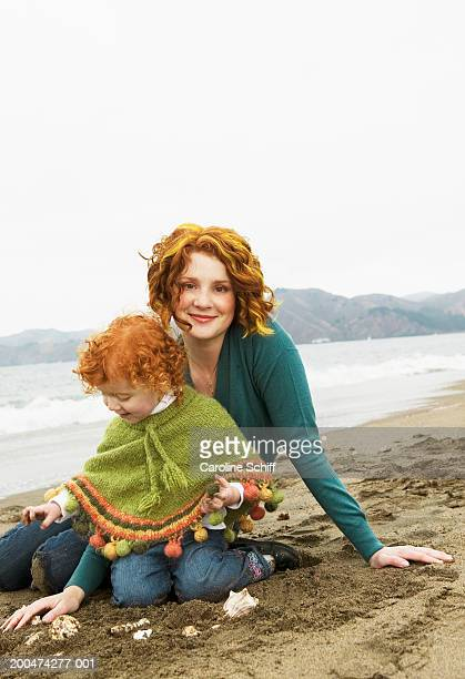 mother and daughter (2-4) playing with shells on beach - caroline roux photos photos et images de collection