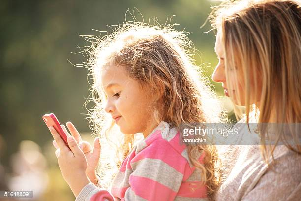 Mother and daughter playing with smartphone outdoors