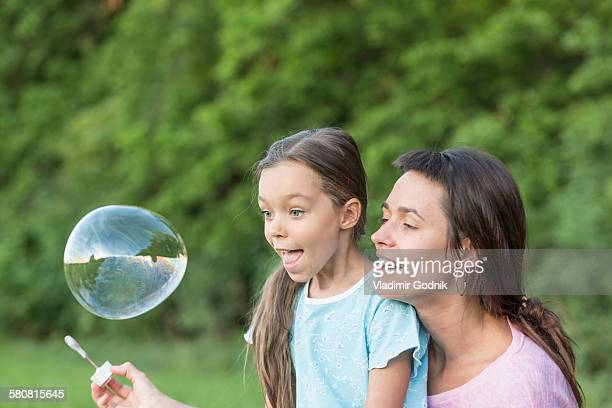 Mother and daughter playing with soap bubble outdoors