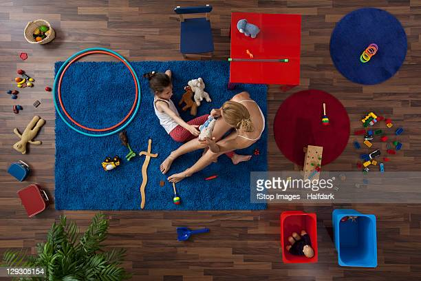 A mother and daughter playing with toys in a living room, overhead view