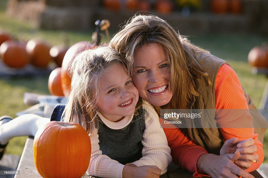 Mother and daughter posing together with pumpkin : Stockfoto
