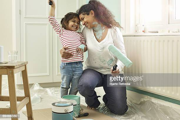 Mother and daughter posing with paint tools