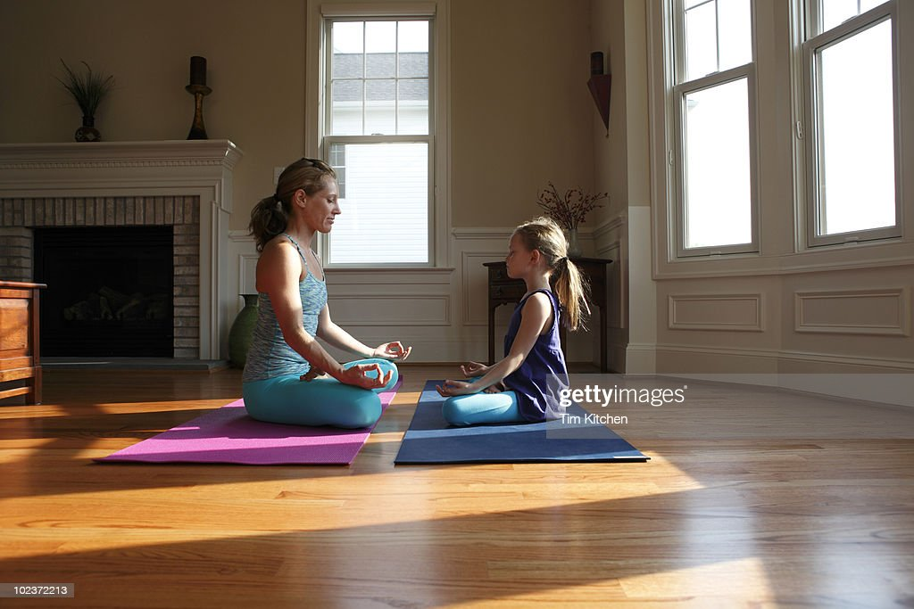 Mother and daughter practicing yoga in home,  : Stock Photo