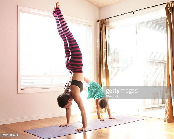 mother and daughter practicing yoga in studio - handstand stock pictures, royalty-free photos & images