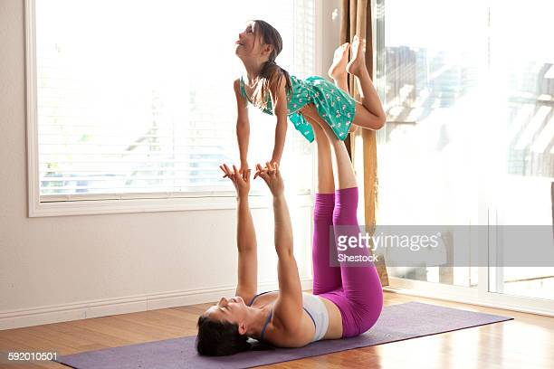 Mother and daughter practicing yoga in studio