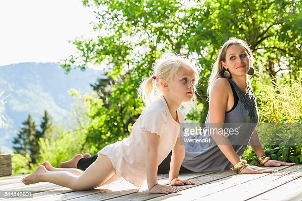 Mother and daughter practicing yoga on wooden terrace