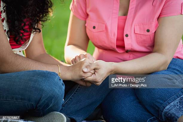 Mother and daughter praying together in a park