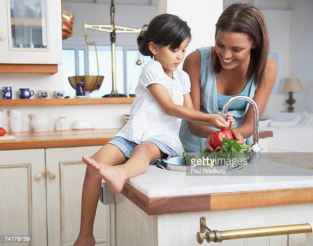 mother and daughter preparing a meal in kitchen - moth stock pictures, royalty-free photos & images