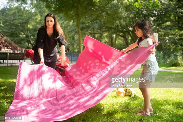 mother and daughter preparing a picnic in the park - picnic blanket stock pictures, royalty-free photos & images