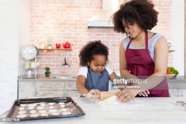 Madre e hija preparar la masa para galletas caseras