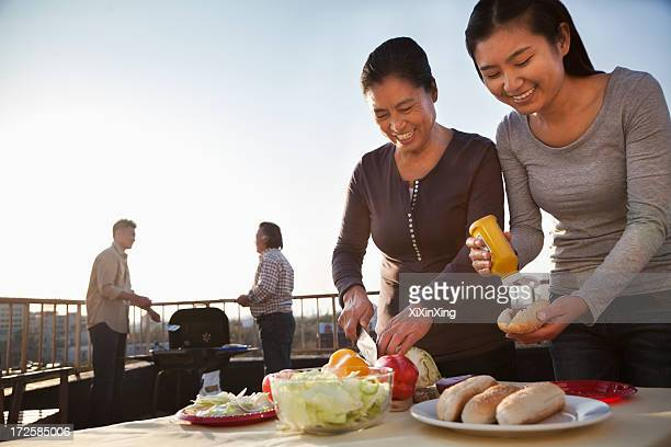 Mother and daughter preparing hot dogs for barbeque, father and son preparing sausages on barbeque