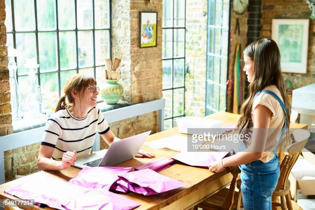 Mother and daughter preparing packages at home