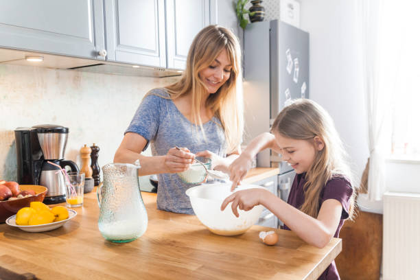 mother and daughter preparing pancakes in kitchen - 焗 預備食物 個照片及圖片檔