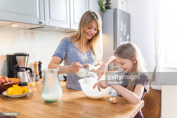 Mother and daughter preparing pancakes in kitchen