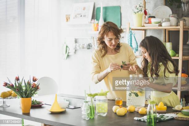 mother and daughter preparing refreshing lemonade together - mint plant family stock pictures, royalty-free photos & images