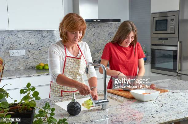 Mother And Daughter Preparing Salad In Kitchen At Home