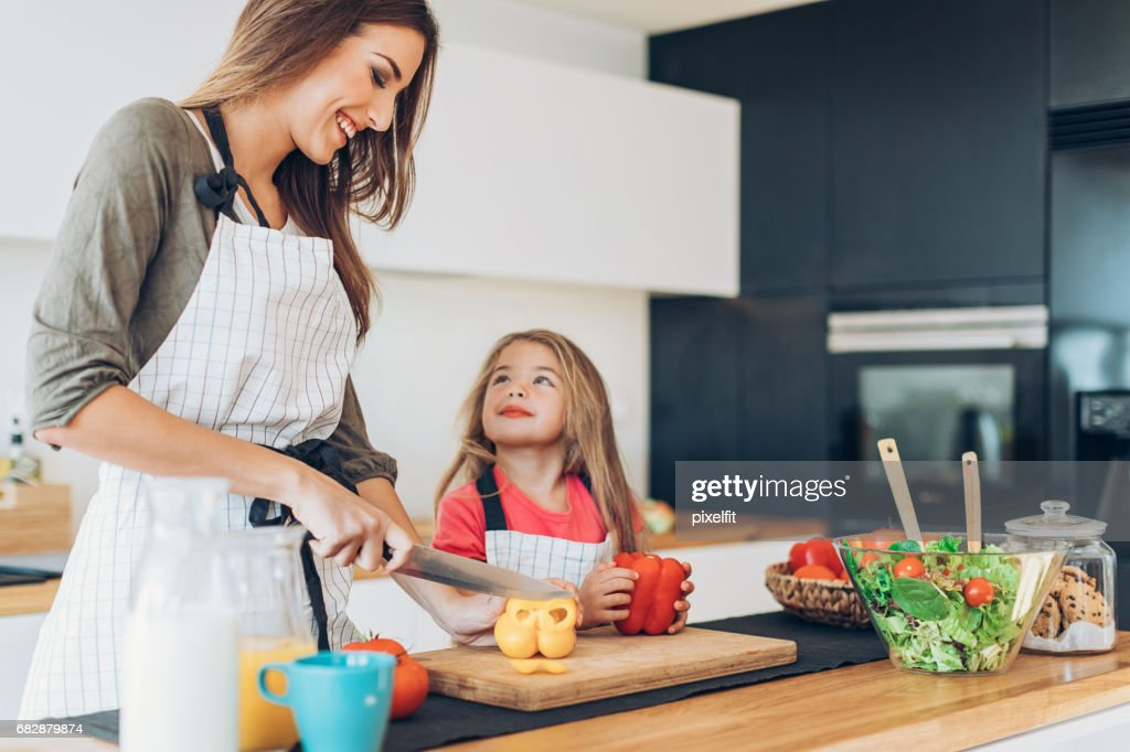 Mother and daughter preparing salad together : Stock Photo