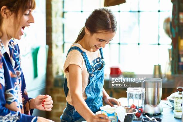 Mother and daughter preparing smoothie in kitchen