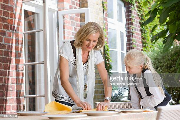 mother and daughter preparing table
