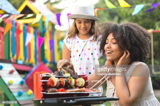 Mother and daughter preparing tasty barbecue on back yard