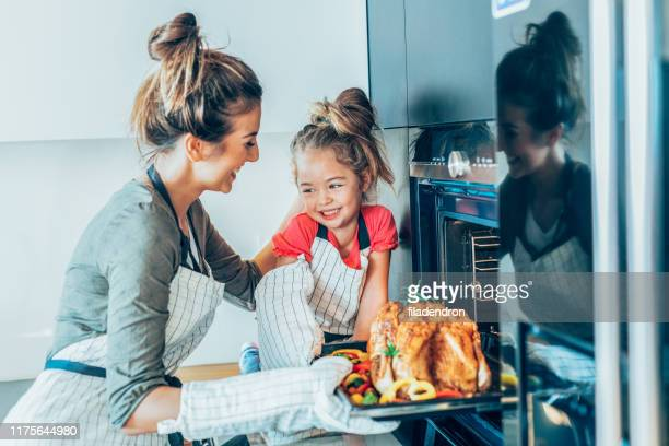 mother and daughter preparing turkey - domestic kitchen stock pictures, royalty-free photos & images