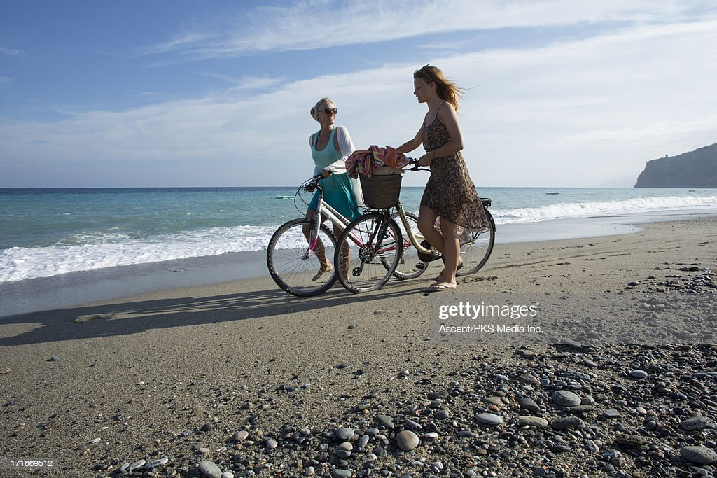 Mother and daughter push bukes along beach edge : Foto stock