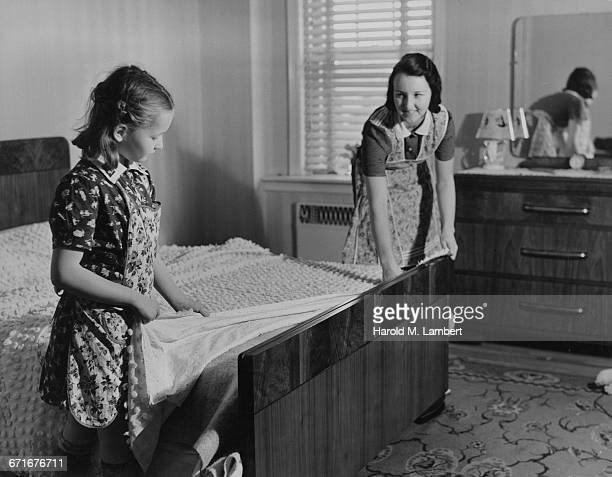 mother and daughter putting bedsheet on bed - {{relatedsearchurl(carousel.phrase)}} ストックフォトと画像